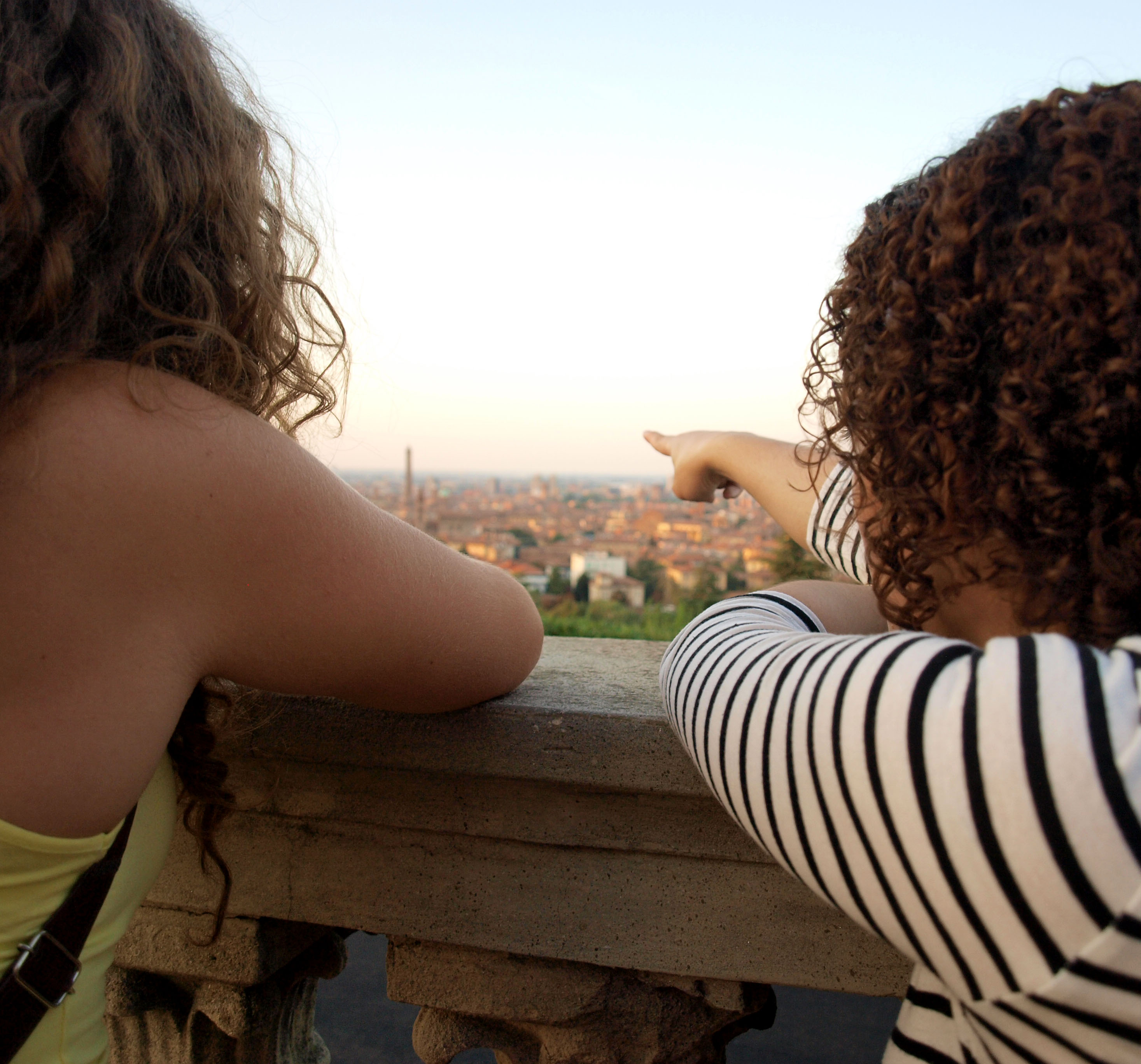 Students point out the iconic medieval tower of Bologna from a scenic viewpoint